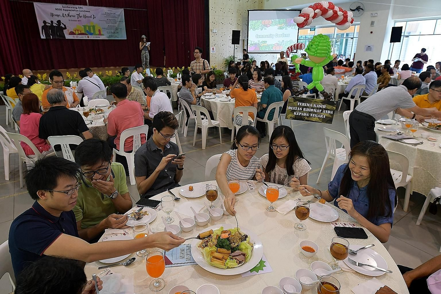 NSmen and their families tucking in to a lunch cooked using vegetables from a community garden, at Woodlands Galaxy Community Club yesterday.