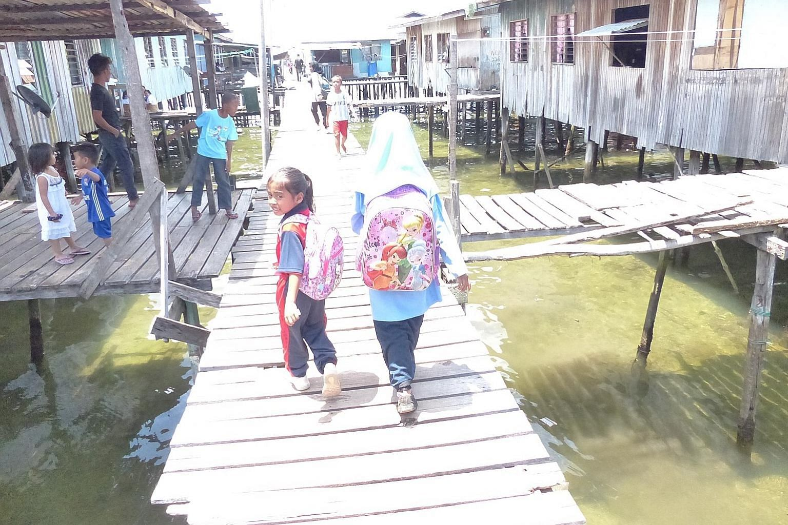 Parti Warisan Sabah leader Shafie Apdal (left) must contend with Umno's Tan Sri Musa Aman, Sabah's Chief Minister, who is credited for his effective management of the state's economy. Kampung Pasir Putih, the enclave of stilt houses on an island just