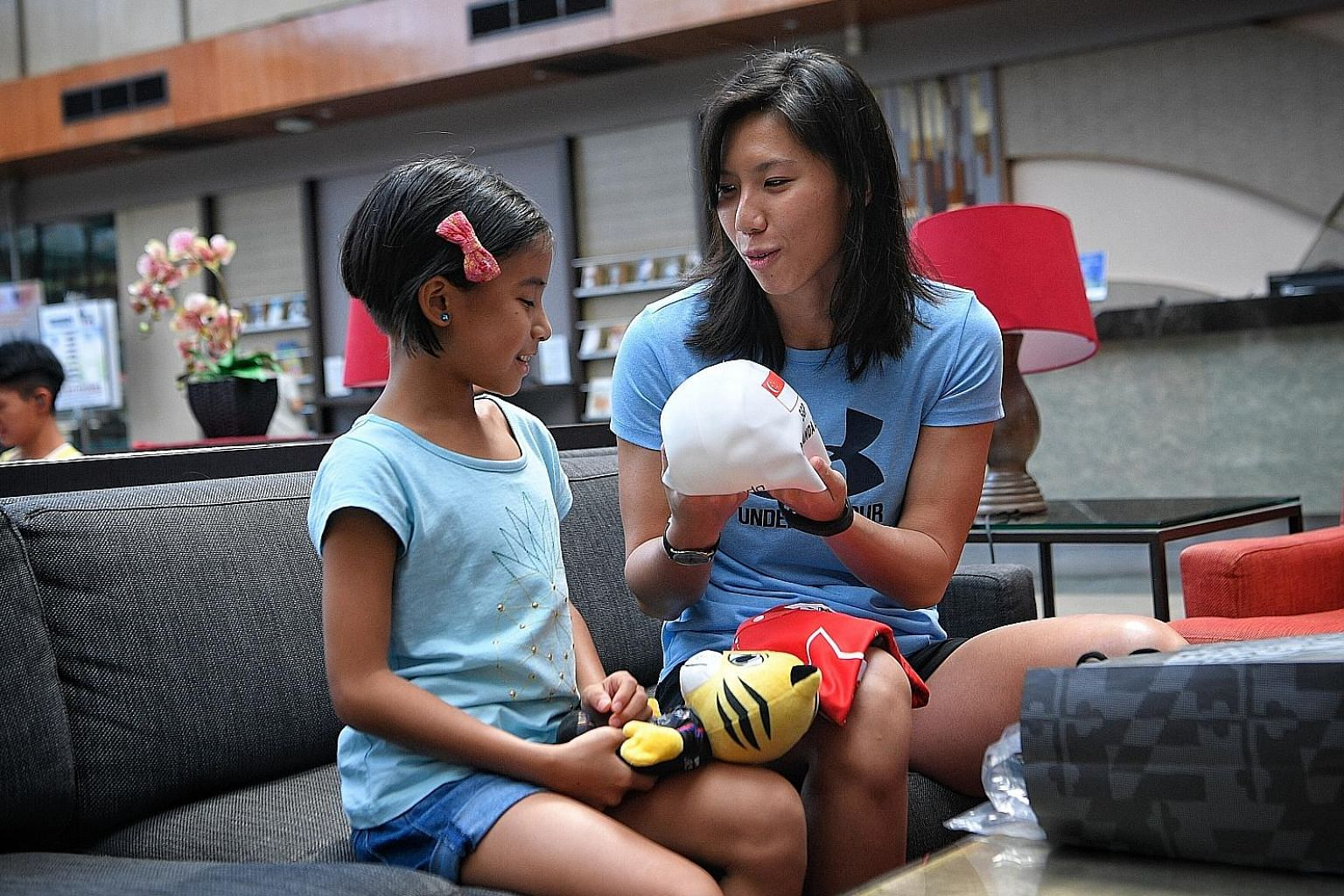 Amanda Lim, who has won every SEA Games 50m freestyle gold since 2009, giving Caitlin a gift bag containing a signed Rimau soft toy, swim cap and a Games jersey with a handwritten message on it.