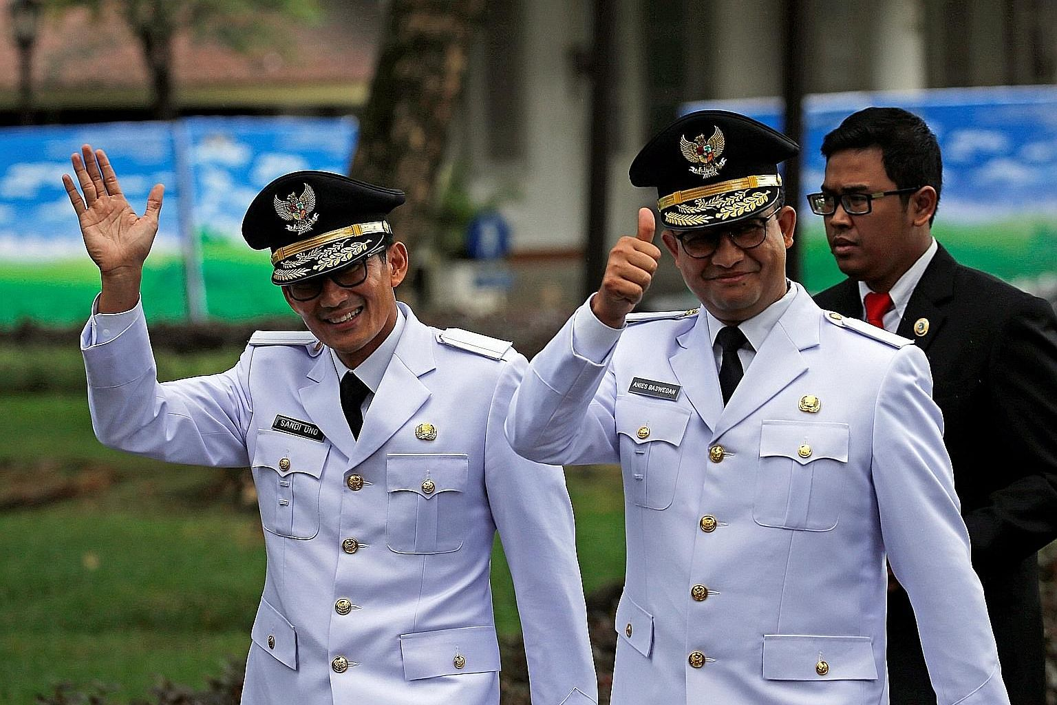 Jakarta Governor Anies Baswedan (far right) and his deputy Sandiaga Uno greeting the media before being sworn in at the Presidential Palace in Jakarta yesterday.