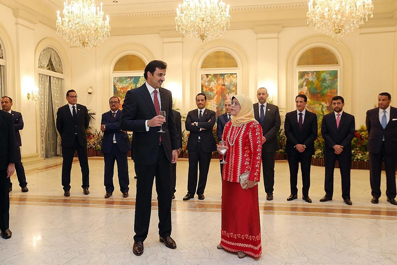 Qatari Emir Sheikh Tamim Bin Hamad al-Thani meeting President Halimah Yacob at a reception at the Istana yesterday. He thanked Madam Halimah for her interest in supporting the friendship between both countries. Sheikh Tamim with Prime Minister Lee Hs