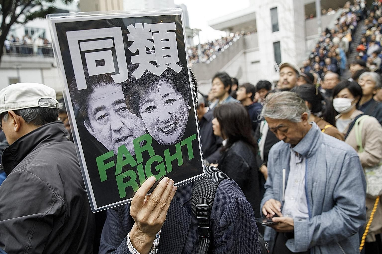 "A man holding up a sign featuring Japanese Prime Minister Shinzo Abe and Tokyo Governor Yuriko Koike under the words ""same kind"" at a rally for the CDPJ in Tokyo. The party's founder stresses commitment to individual civil rights, rather than obligat"