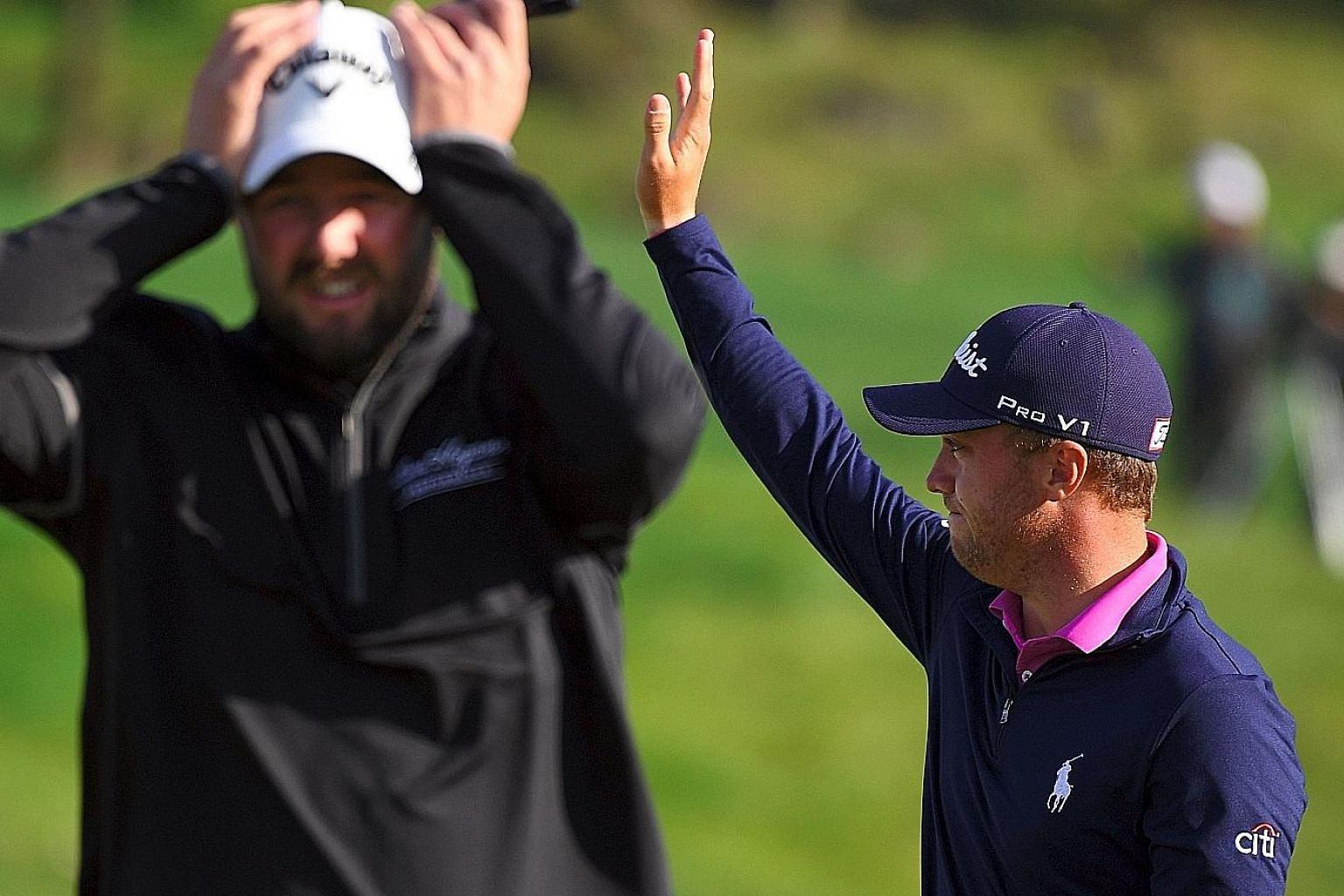 American Justin Thomas waving to celebrate his victory as Australian Marc Leishman rues his poor second shot which found water on the second play-off hole in the CJ Cup at Nine Bridges in Jeju Island.