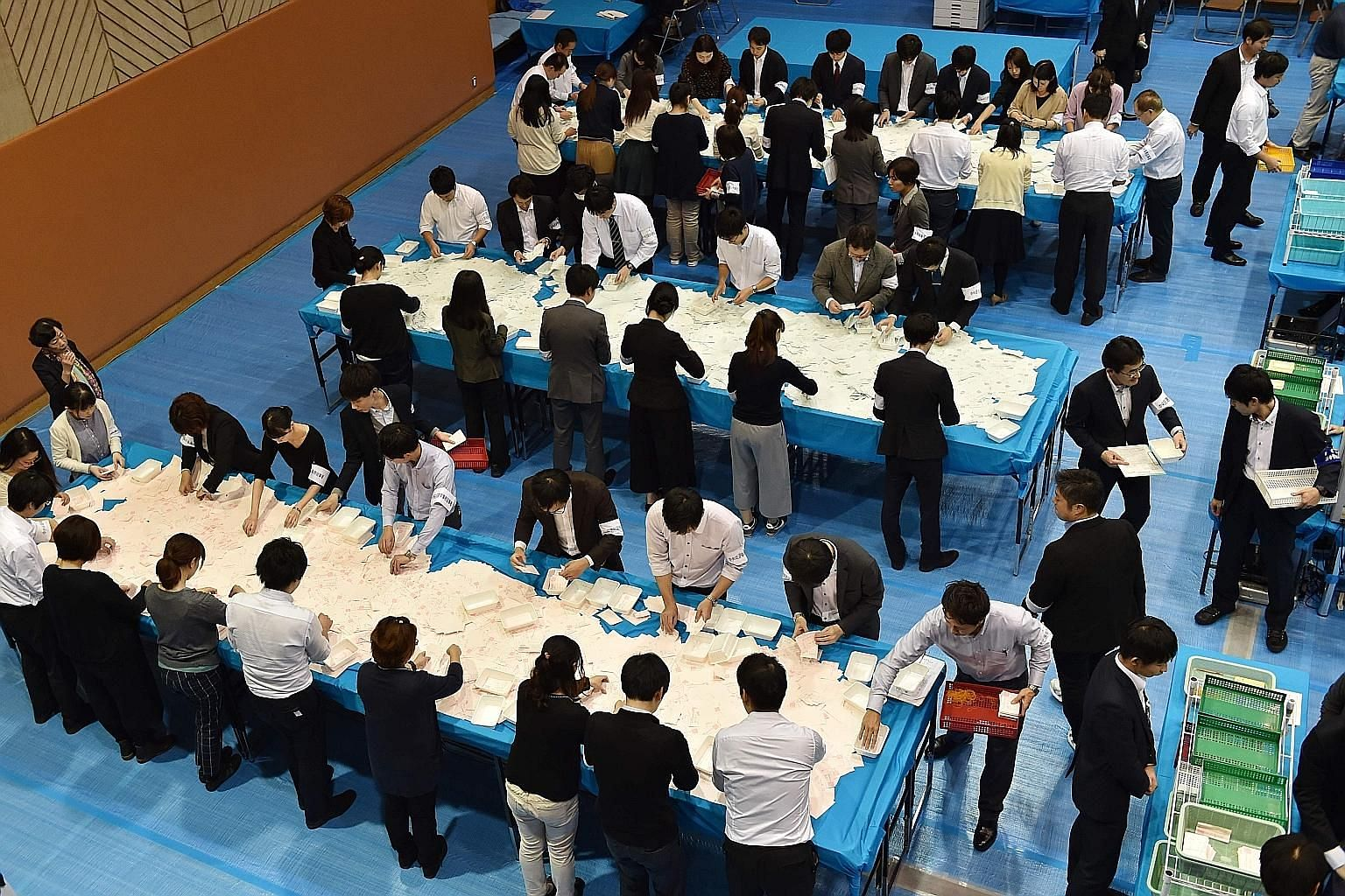 """Officials counting ballot papers at an election office in Tokyo yesterday. The LDP-led coalition has secured a two-thirds """"super majority"""" in the powerful Lower House of Parliament."""