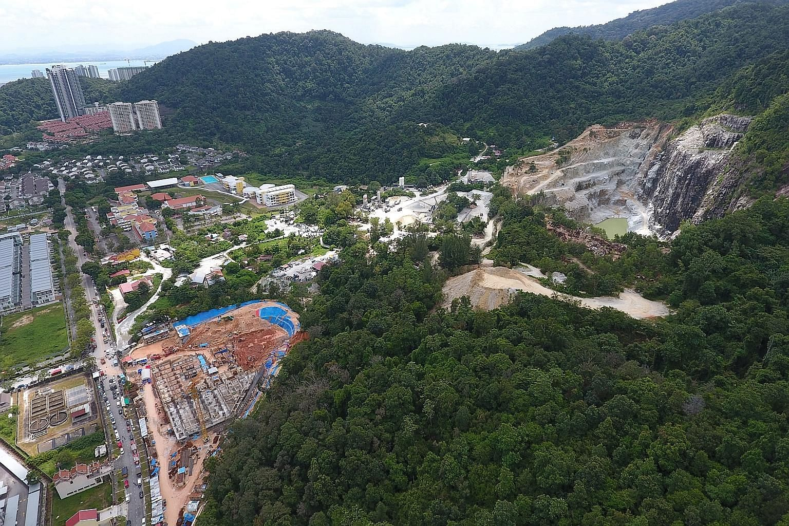 The construction site in Penang where the landslide occurred (left), with a quarry on the right. Malaysia's environment ministry says it had earlier rejected an application by the developer to build on the site because it was next to an active granit