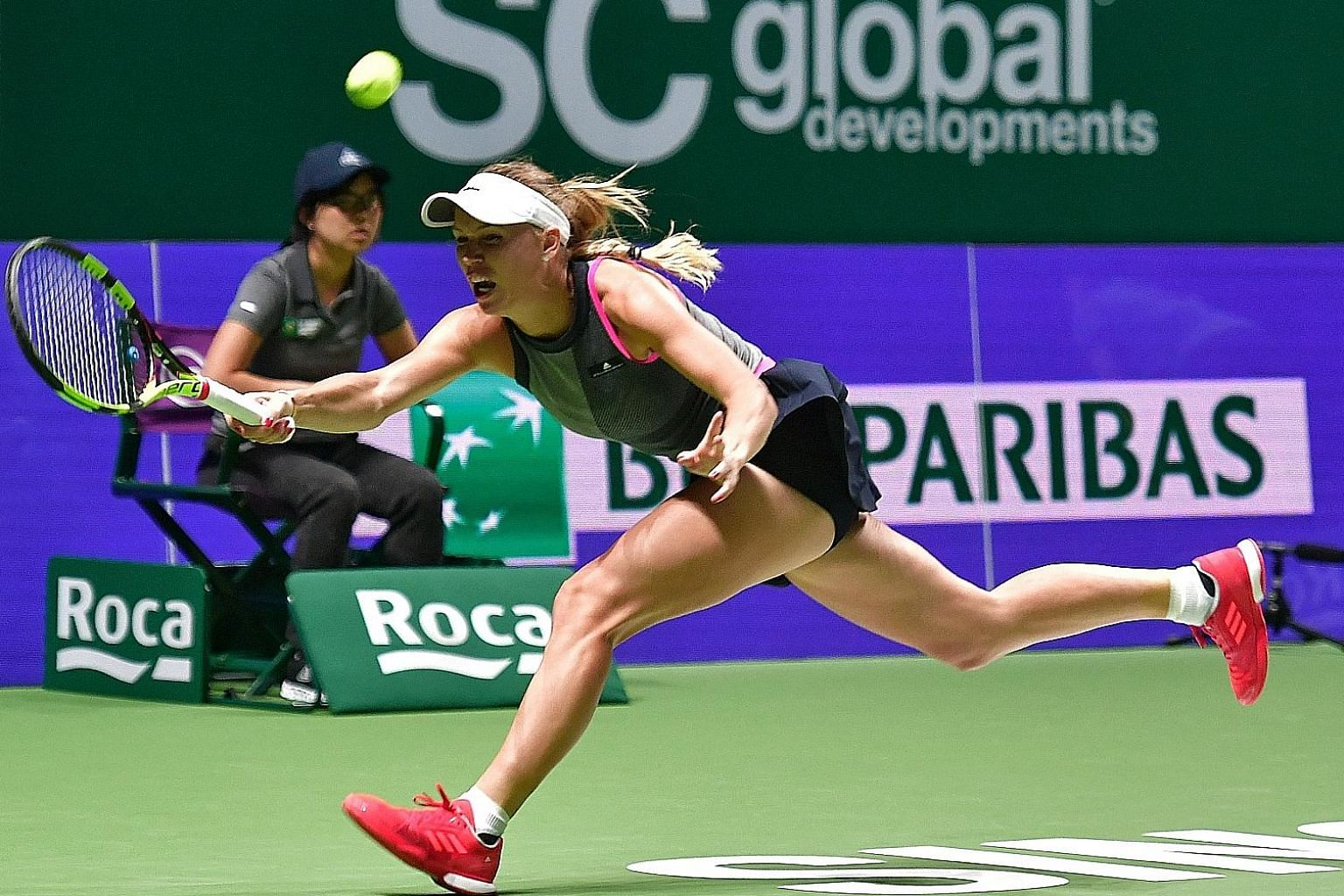 Former world No. 1 Caroline Wozniacki stretching to return a shot from Elina Svitolina in their WTA Finals match last night. The Dane easily won 6-2, 6-0 for her first victory over the Ukrainian.