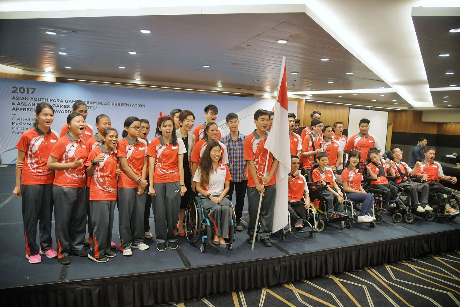 Minister for Culture, Community and Youth Grace Fu, Asian Youth Para Games (AYPG) chef de mission Yip Pin Xiu (front) and athletes at the AYPG flag presentation ceremony held at the Suntec Singapore Convention and Exhibition Centre yesterday. The Dec