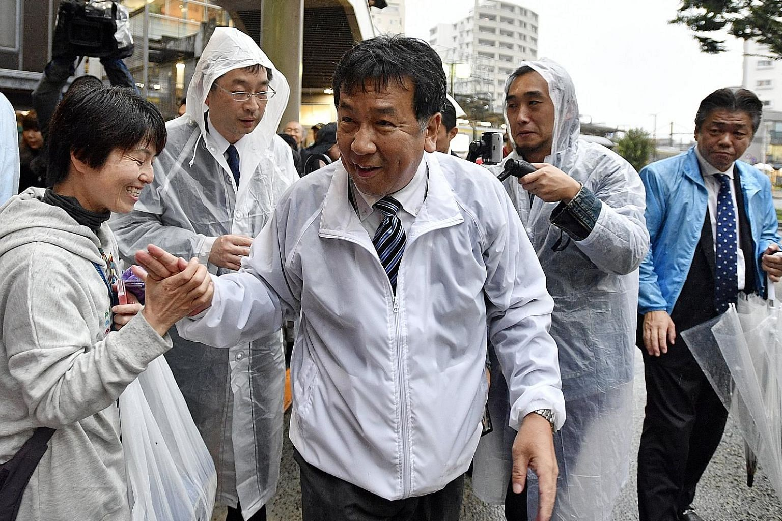 Constitutional Democratic Party of Japan leader Yukio Edano (with striped tie) greeting a supporter after he delivered a speech for his party's candidate in Tokyo on Oct 21. The one-month-old party fielded 78 candidates in the Oct 22 elections and wo