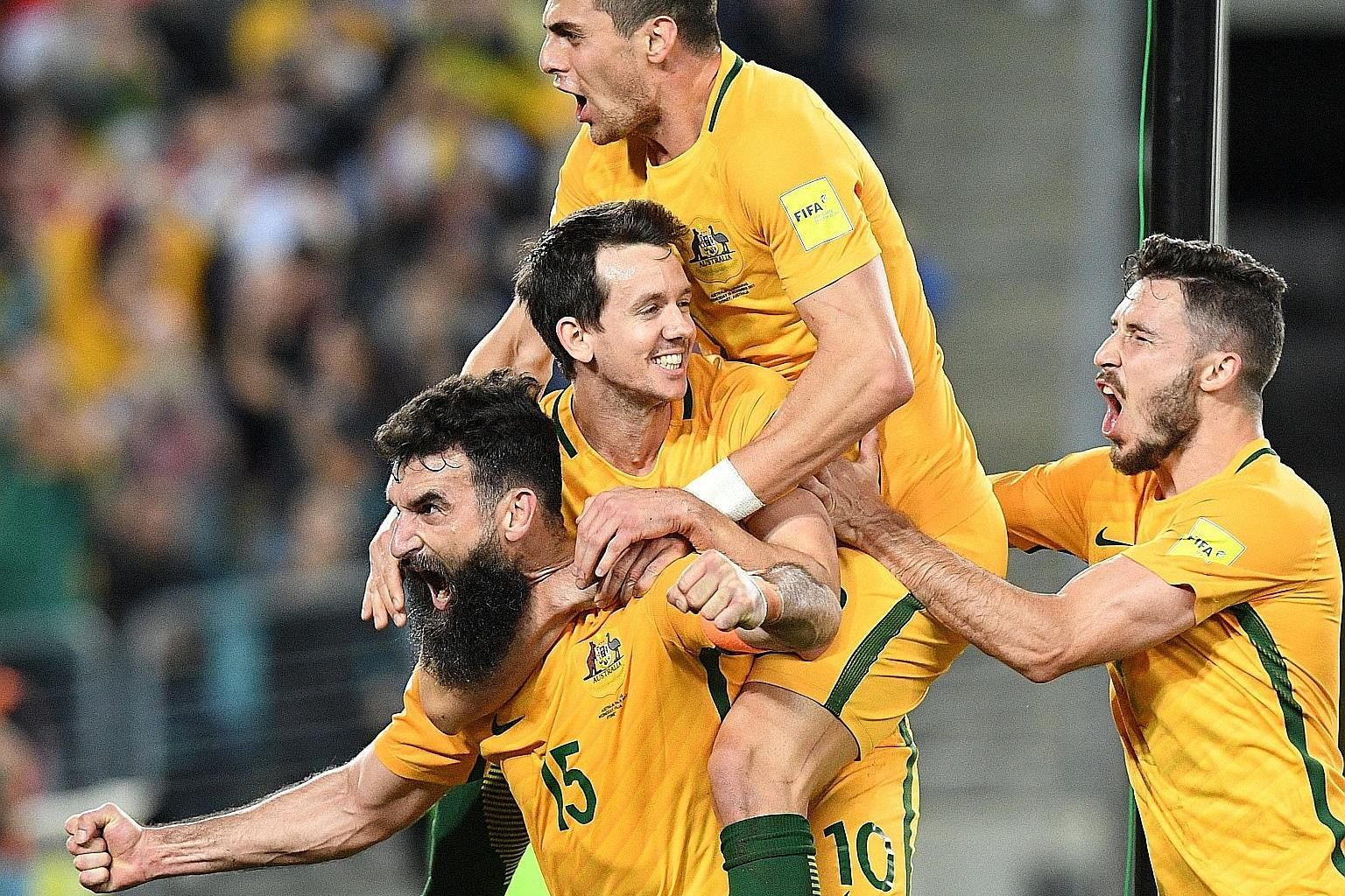 Australia skipper Mile Jedinak (bearded) carrying team-mates Robbie Kruse and Tomi Juric, and his country's World Cup hopes after scoring against Honduras.