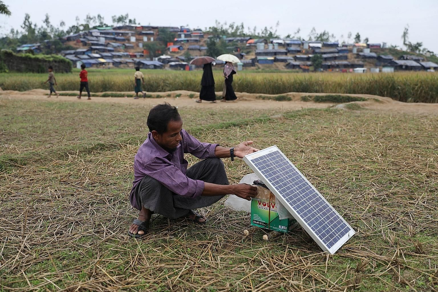 A Rohingya refugee using a solar panel to charge his mobile phone at the Palong Khali refugee camp in Cox's Bazar. Some refugees relied on their phones for information on safe routes to take while fleeing Myanmar.