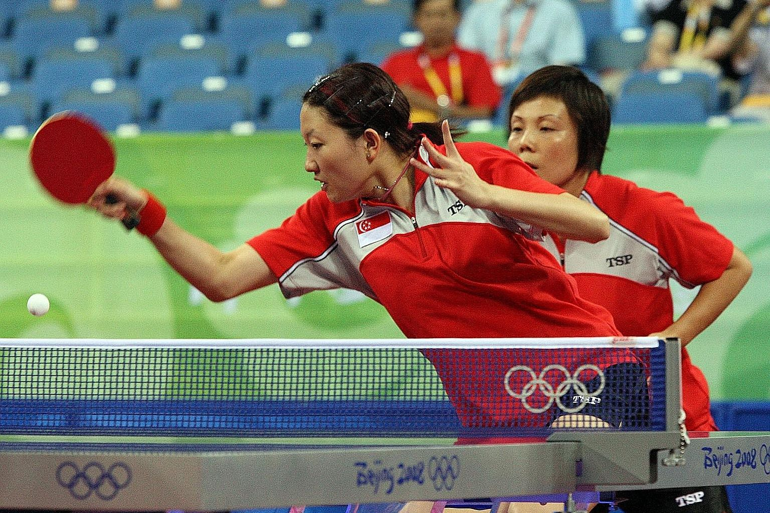 Li Jiawei (front) and Wang Yuegu on the way to winning their match to help Singapore to a 3-2 victory over South Korea in the semi-finals of the Beijing Olympics.