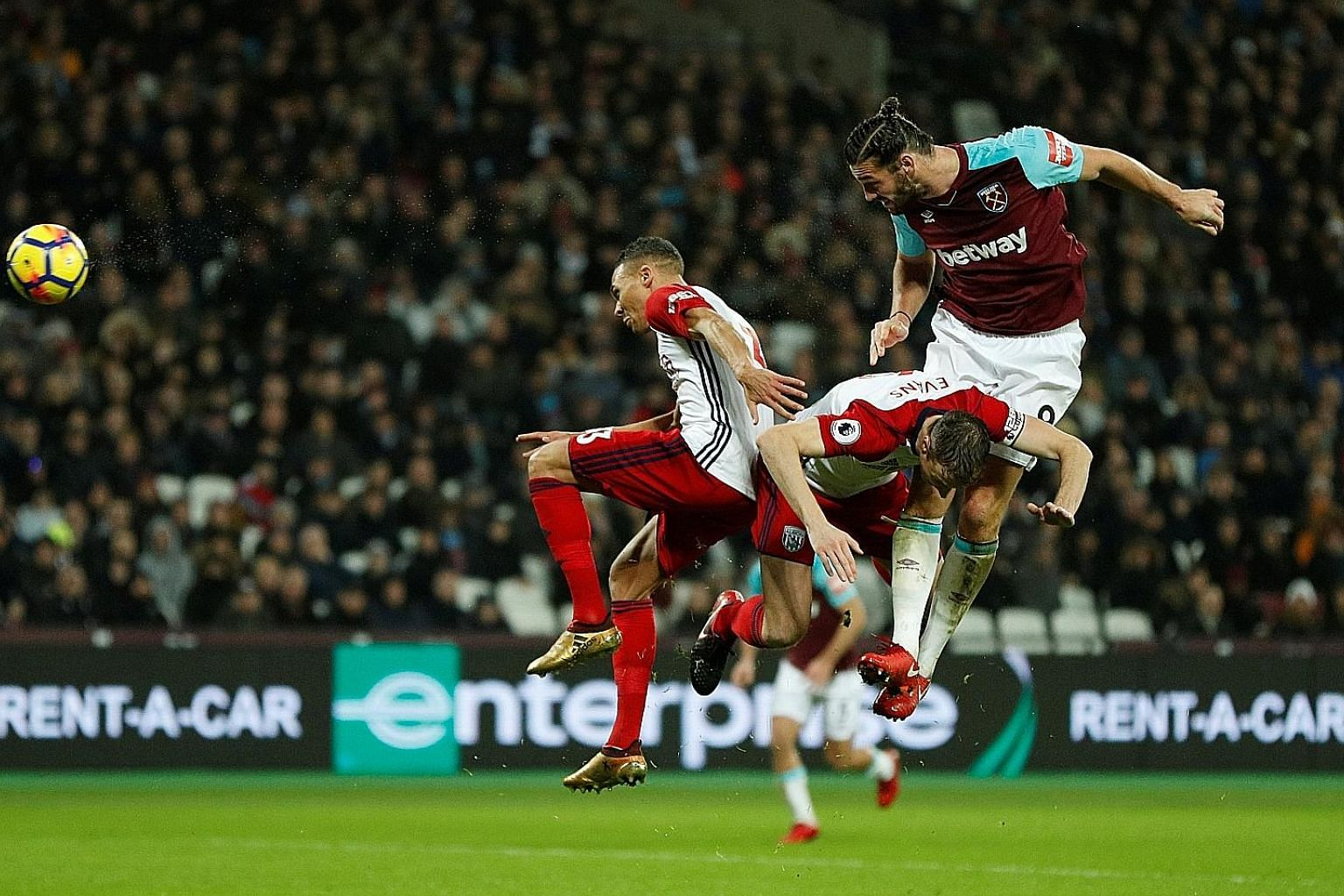 West Ham's Andy Carroll outjumping West Brom defenders Jonny Evans (centre) and Kieran Gibbs to equalise. The English striker later completed the comeback with a stoppage-time winner as the Hammers ended a four-game winless run.
