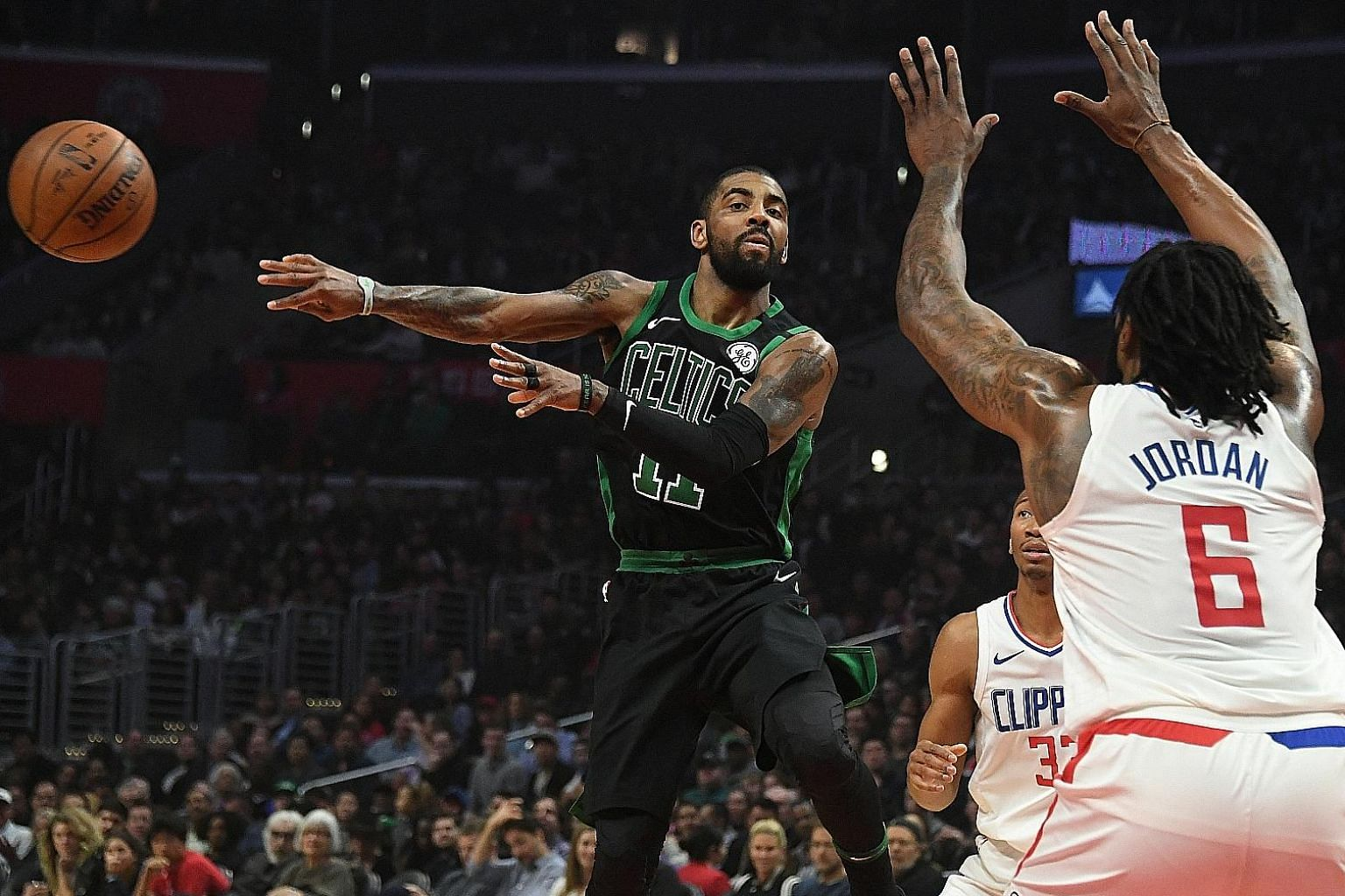 Boston Celtics point guard Kyrie Irving making a no-look pass to evade the defence of Los Angeles Clippers centre DeAndre Jordan during the first half of their National Basketball Association game at the Staples Centre. Irving scored 20 points as fiv