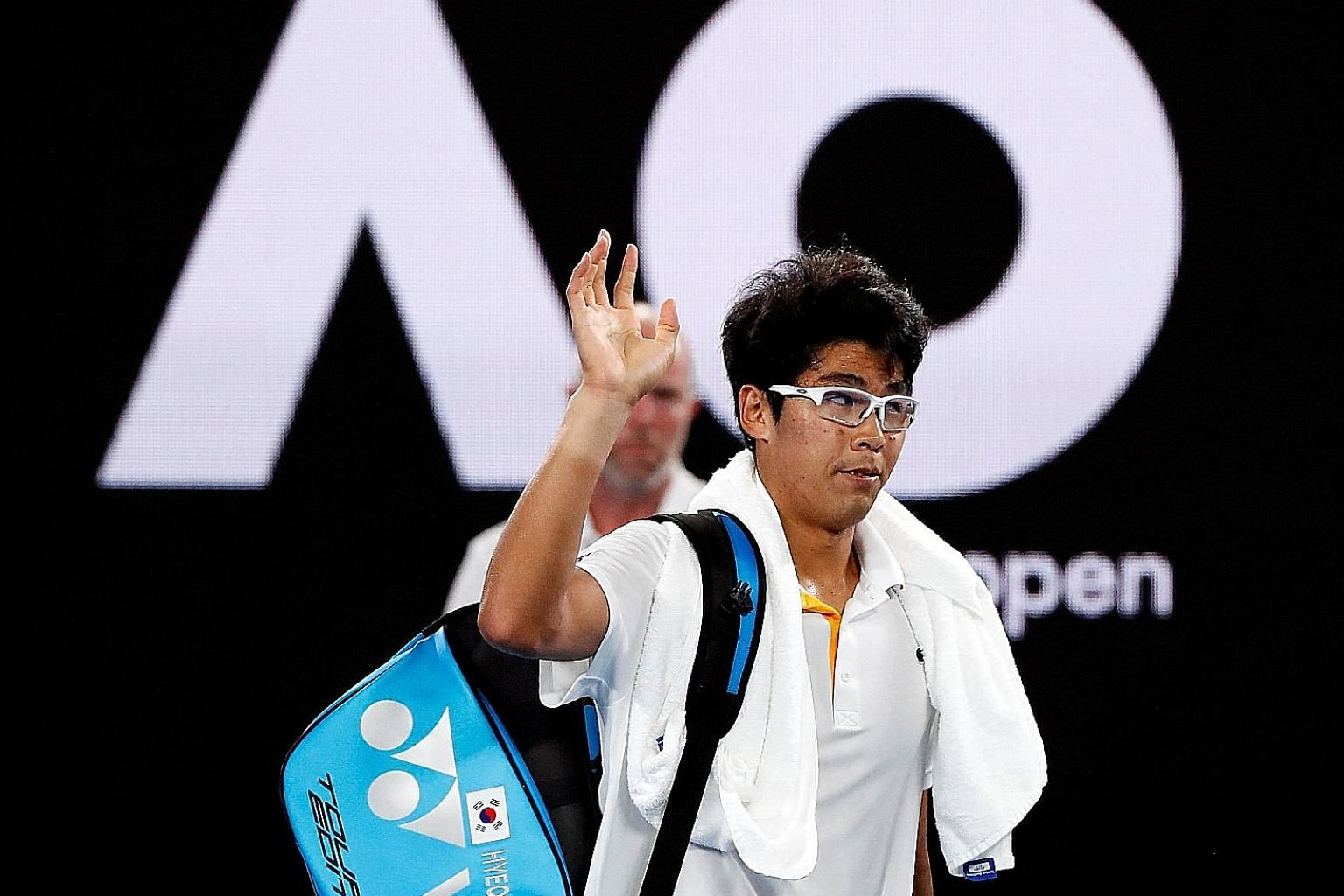 Chung Hyeon leaving the Rod Laver Arena in Melbourne yesterday after retiring injured against Swiss legend Roger Federer in the semi-finals.