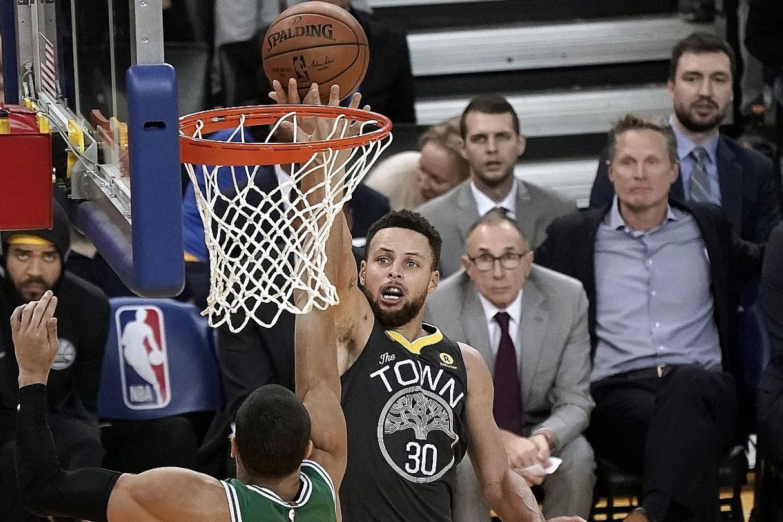 Golden State guard Stephen Curry shoots over Boston forward Jayson Tatum as guard Kyrie Irving looks on during their NBA game at Oracle Arena on Saturday. Curry says he and Irving bring the best out of each other.