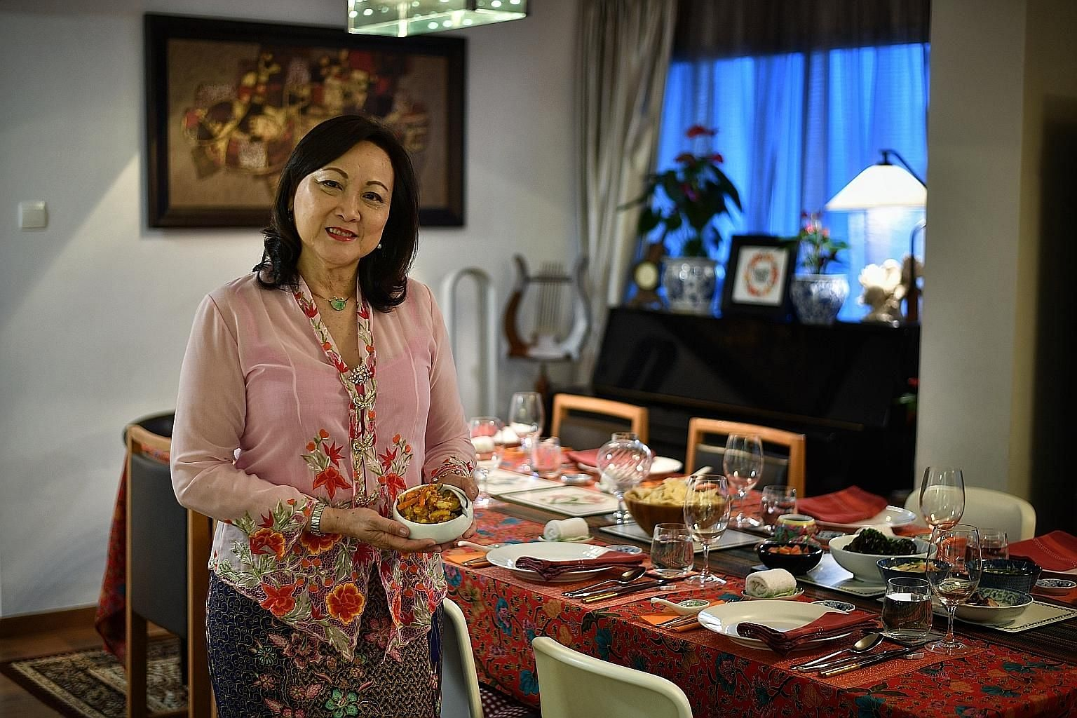 Lynnette Seah (seen with her achar, or pickled vegetables) serves Peranakan and Western meals in her flat in Tiong Bahru.
