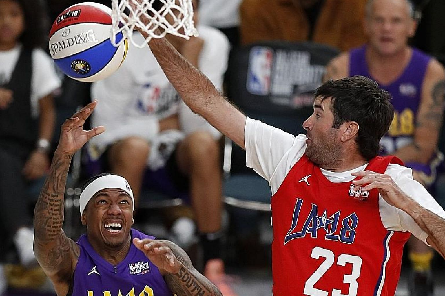 Golfer Bubba Watson blocking a shot by singer Nick Cannon during the NBA All-Star Celebrity Game in Los Angeles on Friday.