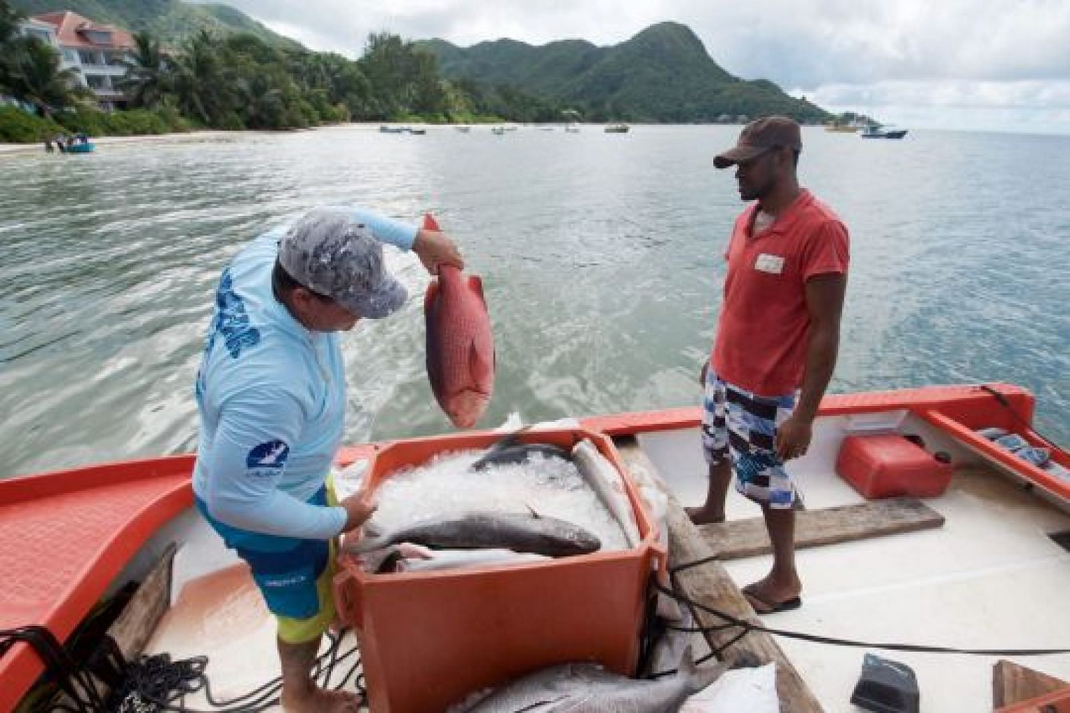 Fishermen sorting their catch in Praslin, one of the islands in Seychelles. The island nation mainly relies on tourism and fishing for revenue, but in recent years, oil and gas companies have been exploring its waters.