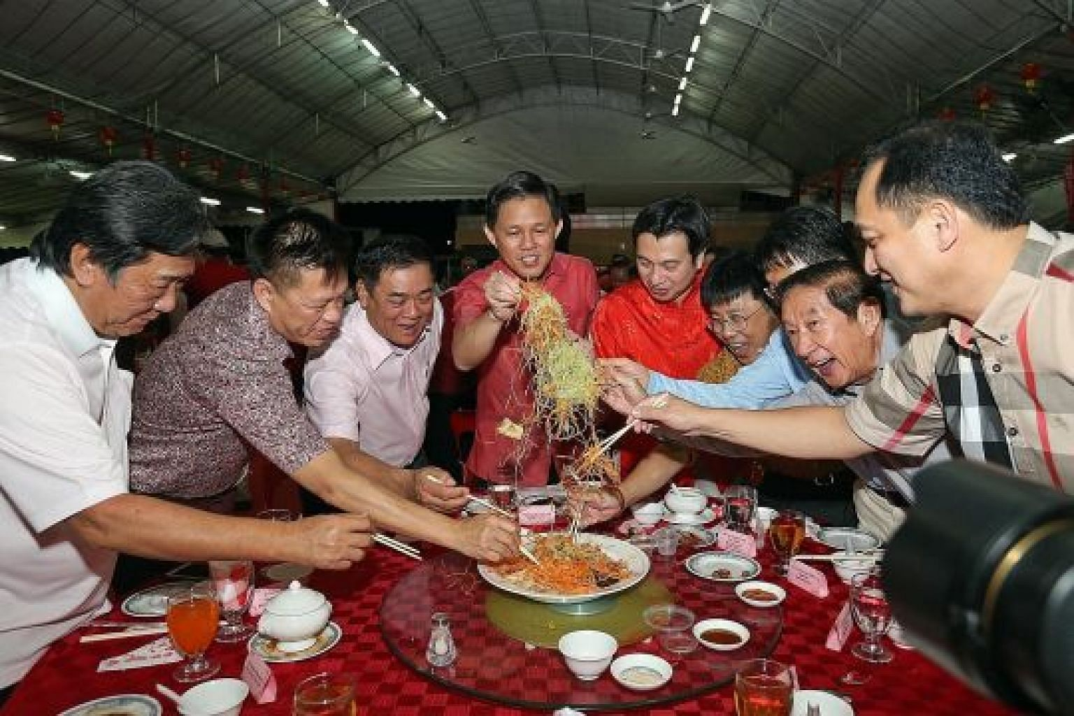 Minister in the Prime Minister's Office Chan Chun Sing (centre) and MP for Tanjong Pagar GRC Chia Shi-Lu (in red) join residents in lo hei at the annual Tanjong Pagar GRC and Radin Mas SMC Lunar New Year Dinner yesterday.