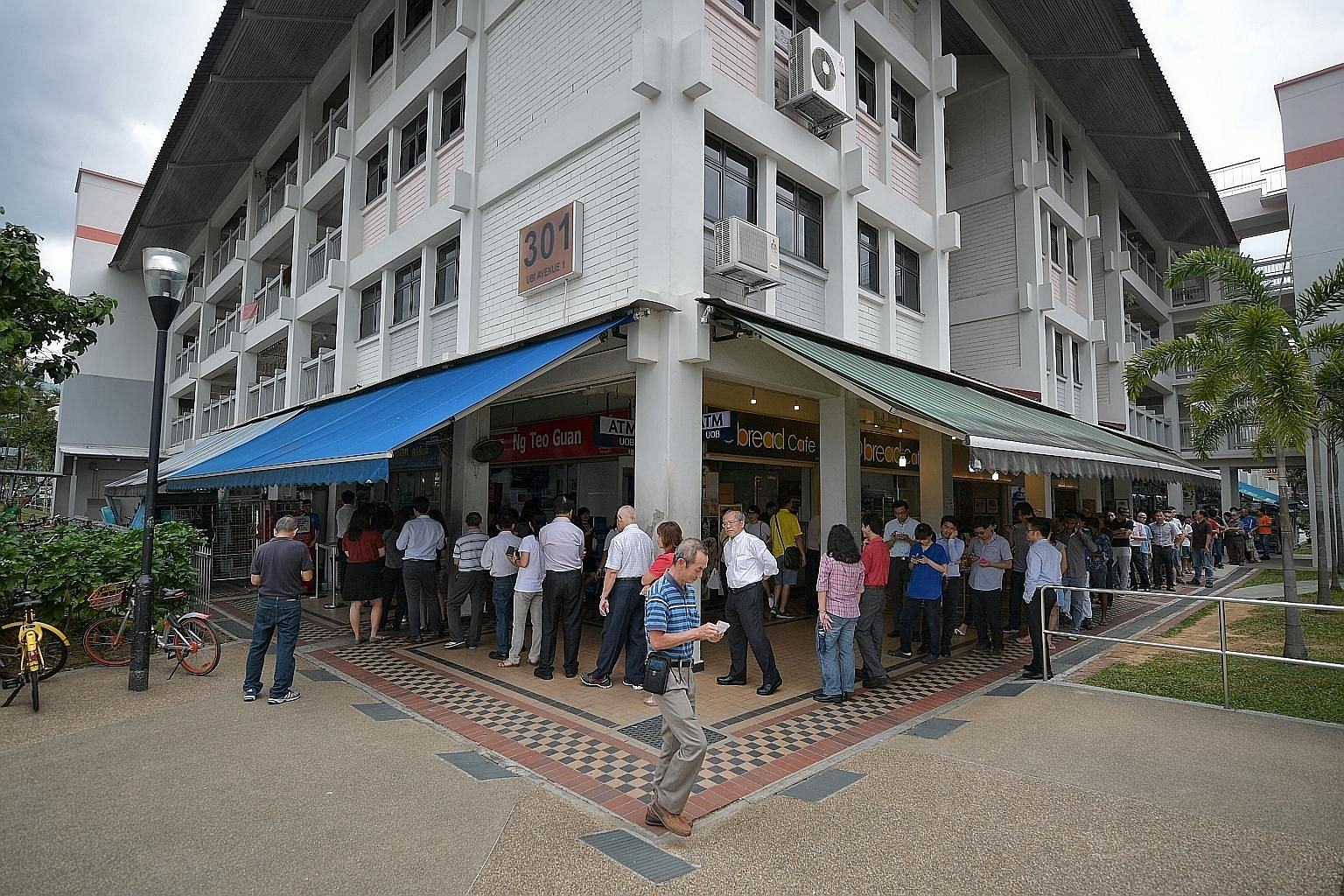 The annual Toto Hongbao Draw, with a top prize of $12 million, drew long queues at several Singapore Pools outlets yesterday, including this one at Block 301, Ubi Avenue 1. Punters hope to strike it rich in the draw tonight. This year's jackpot is le