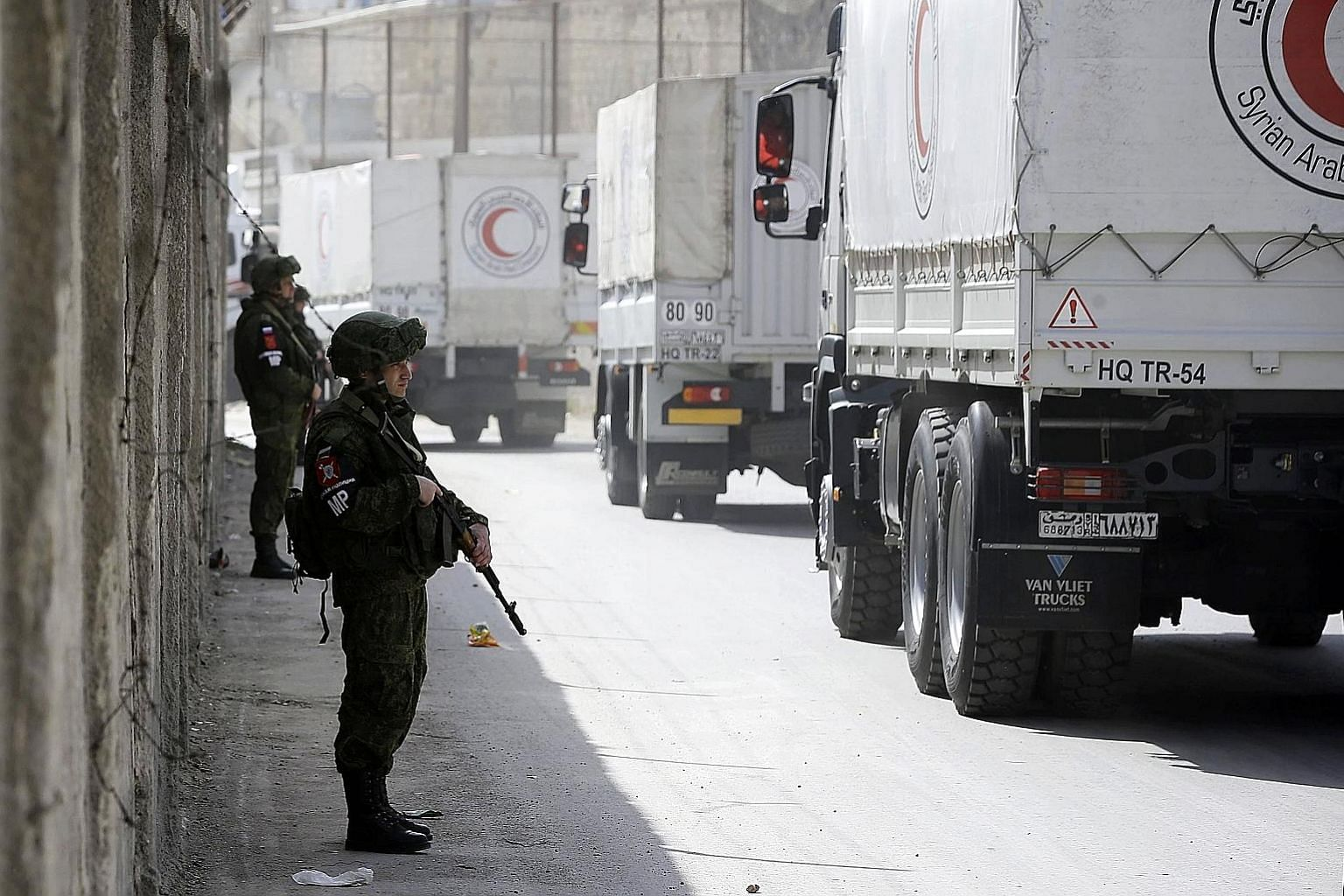 Russian soldiers standing guard as Syrian Arab Red Crescent trucks carrying aid drove by the checkpoint on the outskirts of Damascus neighbouring the eastern Ghouta region, as they headed towards the rebel-held enclave yesterday.
