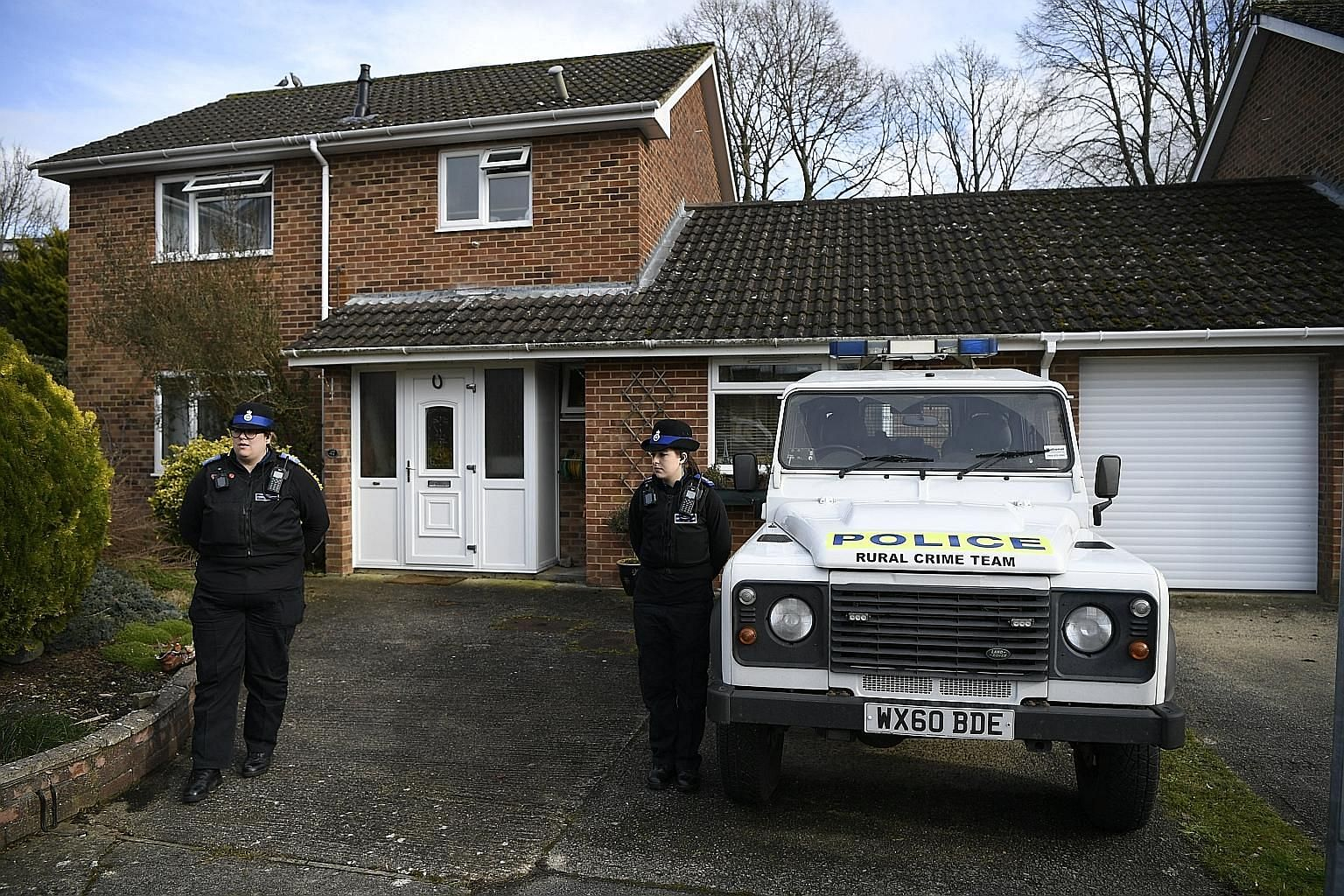 Police standing guard outside what is believed to be the home of former Russian spy Sergei Skripal (above) in Salisbury, Britain, on Tuesday.