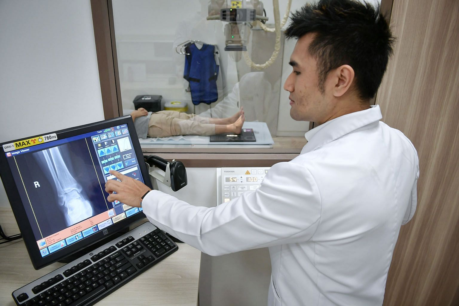 """NHG radiographer Harris Abdul Razak using the digital radiography system to process an X-ray image of a patient's ankle at Ang Mo Kio Polyclinic. X-rays can now be done for 120 patients a day """"without breaking a sweat"""", he says, compared to up to 80"""