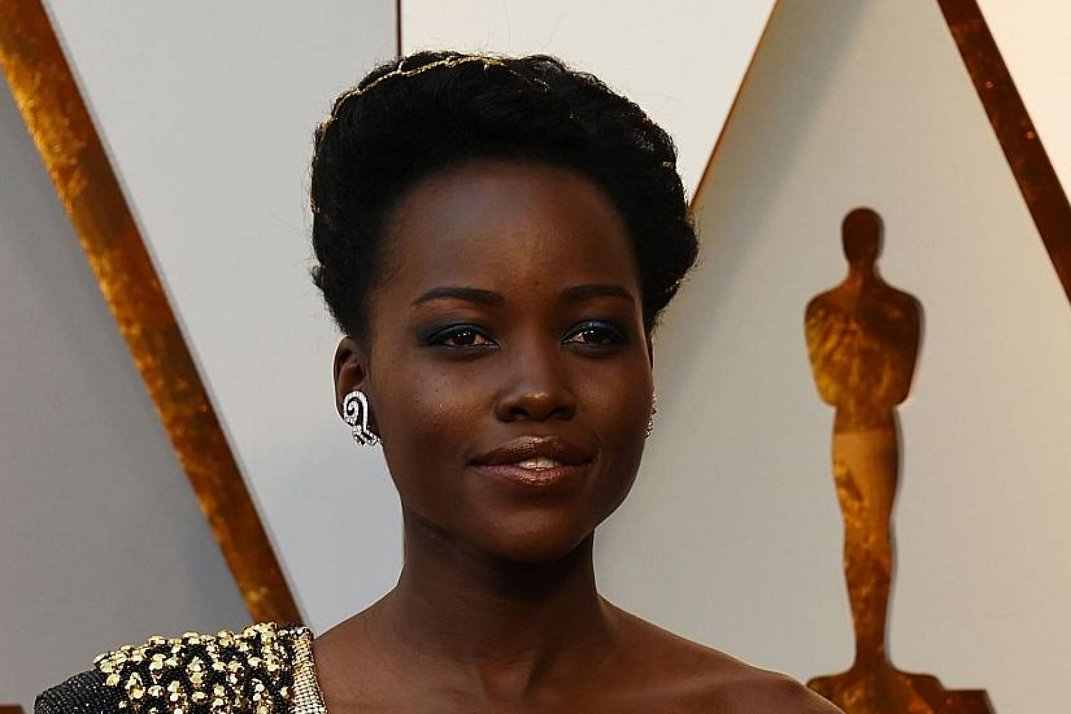 The hint of bronze on actress Lupita Nyong'o's lips echoes her gold dress.