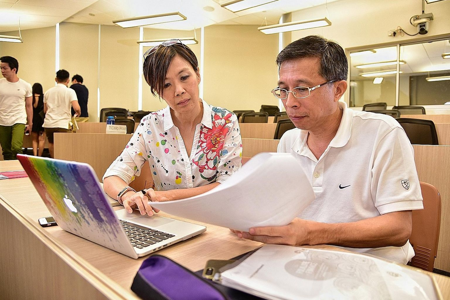 NUS alumni Genevieve Yeep and Lim Swee Hock are taking a business school module in personal finance and private wealth management at the university.