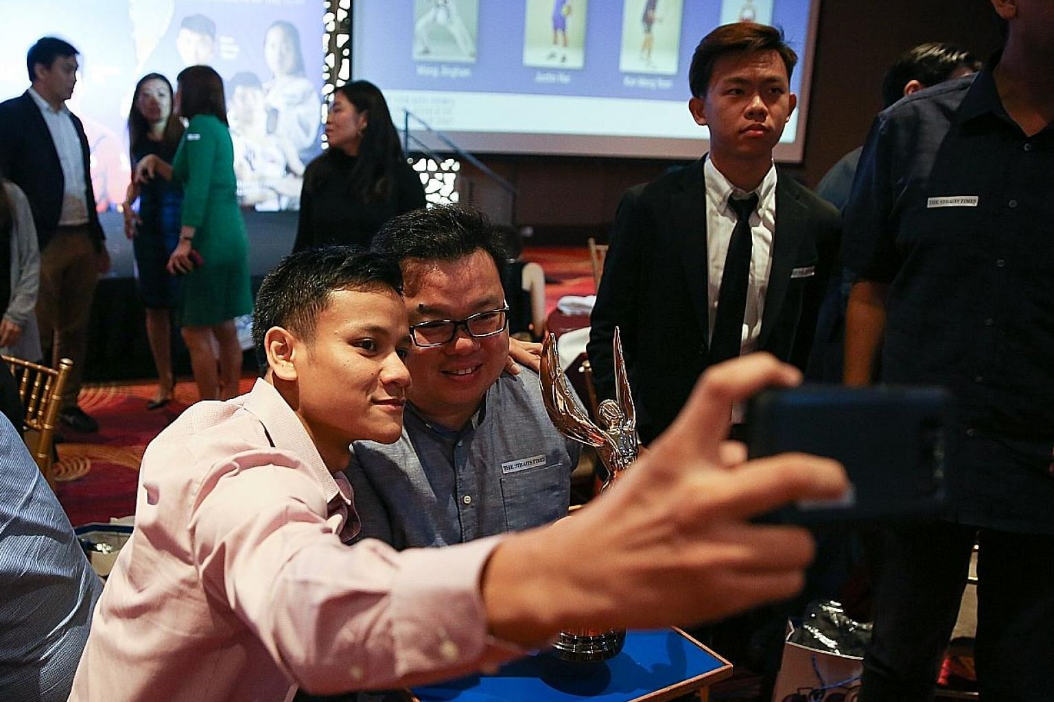 Jason Chee obliging fellow nominee and boxer Muhamad Ridhwan, one of his many wefie hunters, at the Mandarin Orchard Singapore hotel ballroom yesterday.