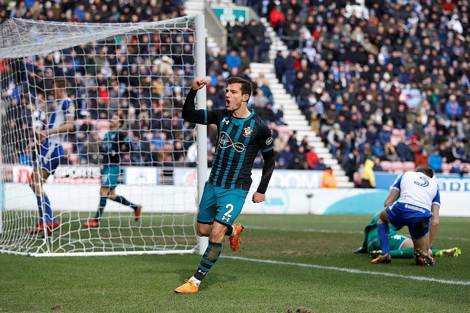 Southampton defender Cedric Soares celebrating after his 91st-minute goal against Wigan sealed a 2-0 win at the DW Stadium yesterday, sending the Saints through to the FA Cup semi-finals for the first time in 15 years. Midfielder Pierre-Emile Hojbjer
