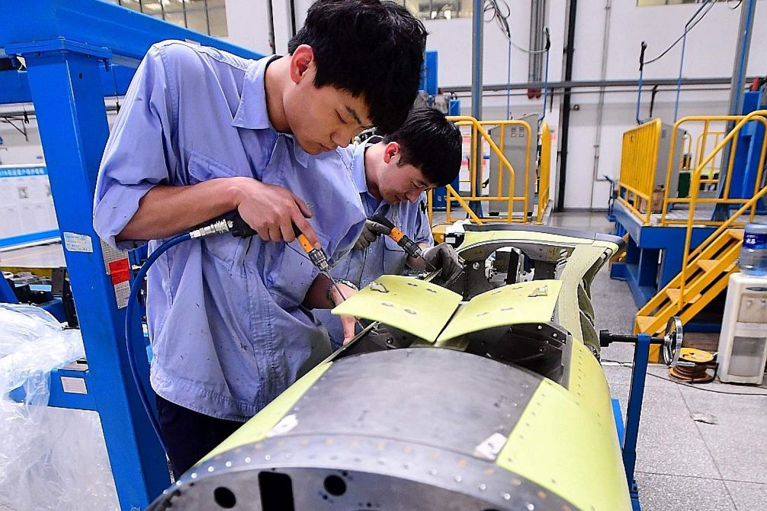 Chinese employees working on the engine of a passenger jet at a factory in Shenyang in China's north-eastern Liaoning province. Thousands of products are made with components sourced from multiple countries. Many of them go to China for final assembl