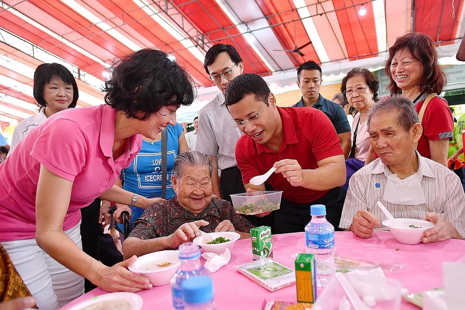 MP for Tanjong Pagar GRC Joan Pereira and Minister for Social and Family Development Desmond Lee serving porridge to Madam Wan Lau Lui, 93, and her friends at Bukit Merah View Square yesterday, as part of the Hot, Happy & Healthy Meal project to help