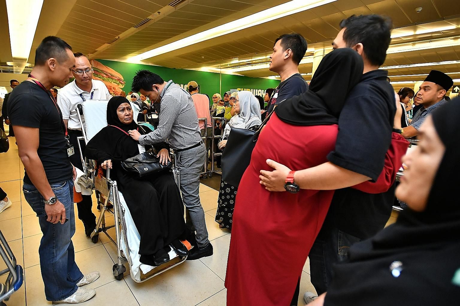 Left: Madam Hasimah Idris, 58, one of the returning pilgrims, being attended to on her arrival at Changi Airport yesterday. Below: Mr Arman Mohamed Hassan, 58, nursing his injured hand. He was among the survivors of the bus crash in Mecca last Tuesda
