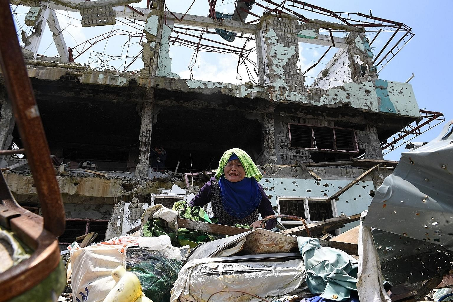 An anguished resident trying to collect salvageable belongings from her destroyed house during a visit yesterday to the main battle area in the southern Philippine city of Marawi. After fleeing for their lives nearly a year ago, residents of the batt