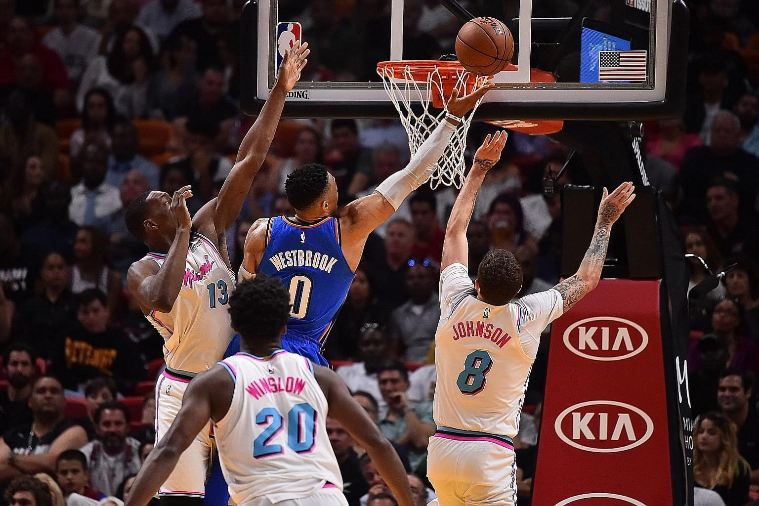 Oklahoma City point guard Russell Westbrook evading the challenges of Miami's Edrice Adebayo and Tyler Johnson for a finger roll. The Thunder sealed their post-season spot with a 115-93 win at the American Airlines Arena.