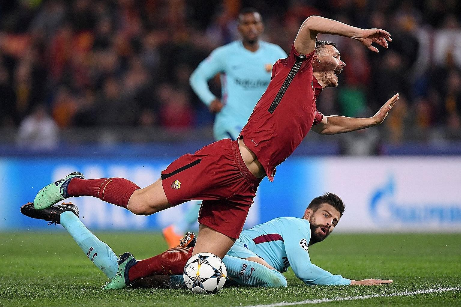 Roma's Edin Dzeko is fouled by Barcelona's Gerard Pique, resulting in a penalty which Daniele de Rossi converted to put his side 2-0 up.