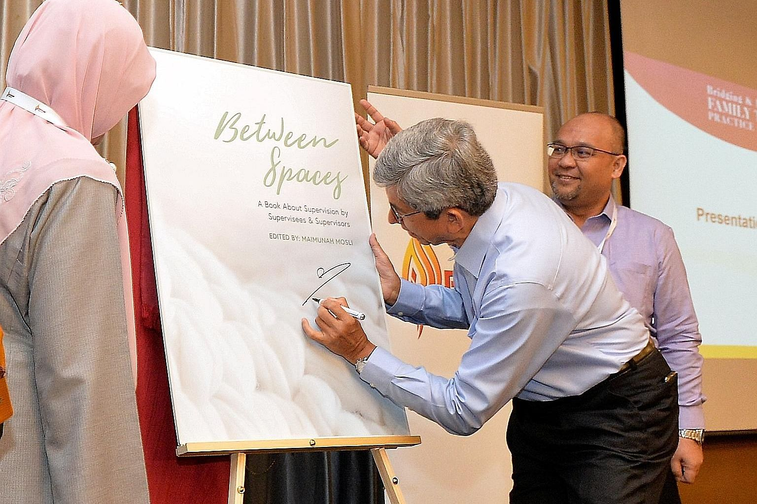 Minister-in-charge of Muslim Affairs Yaacob Ibrahim launching the book Between Spaces at the symposium yesterday, with PPIS chief executive Mohd Ali Mahmood.