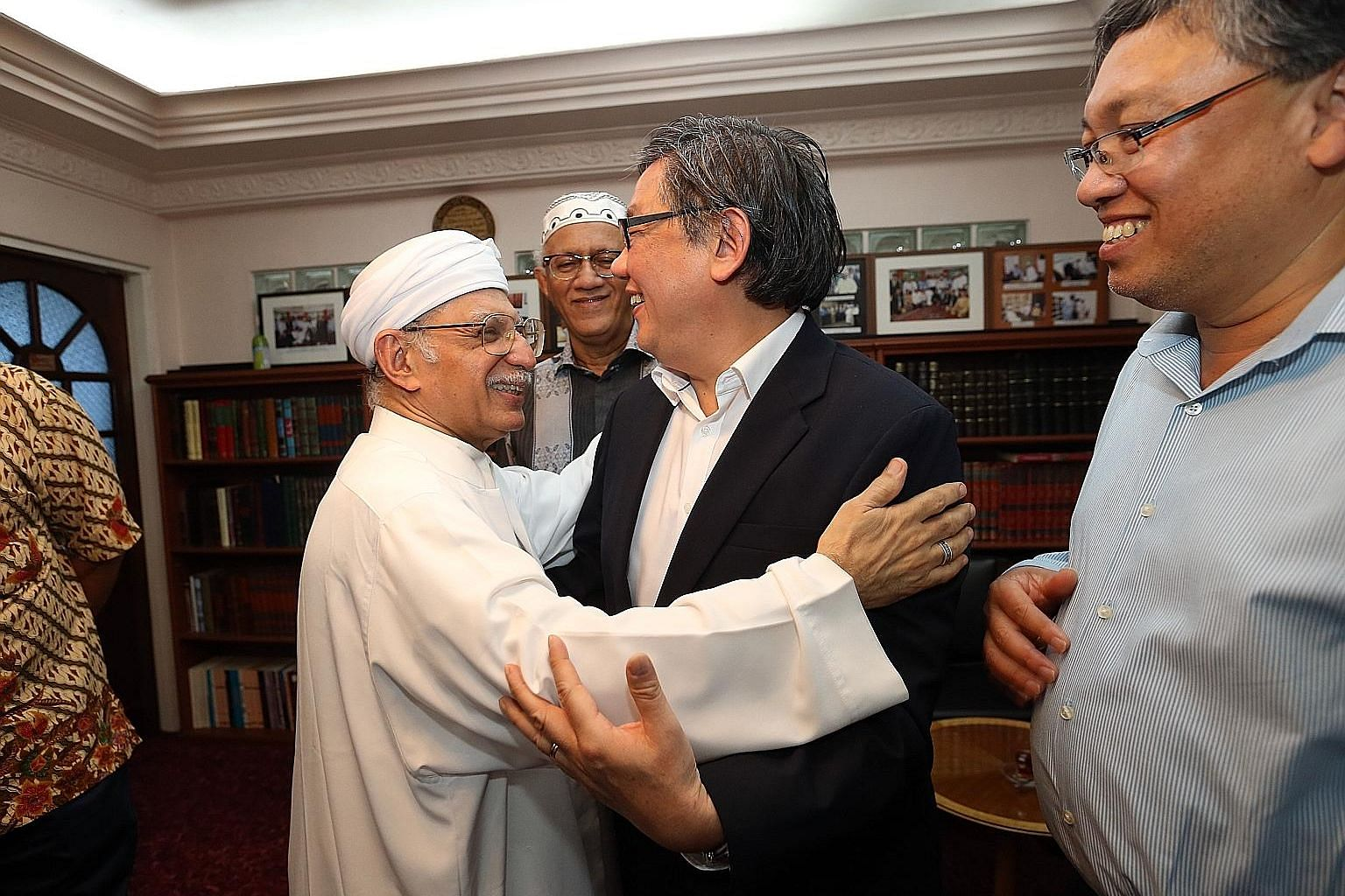 Ba'alwie Mosque's Imam Habib Hassan Al-Attas embracing Pastor Yang Tuck Yoong. Other guests at the meeting included Mr Mohamed Abdullah Alhabshee (centre), the husband of President Halimah Yacob, and Malaysian High Commissioner to Singapore Zulkifli