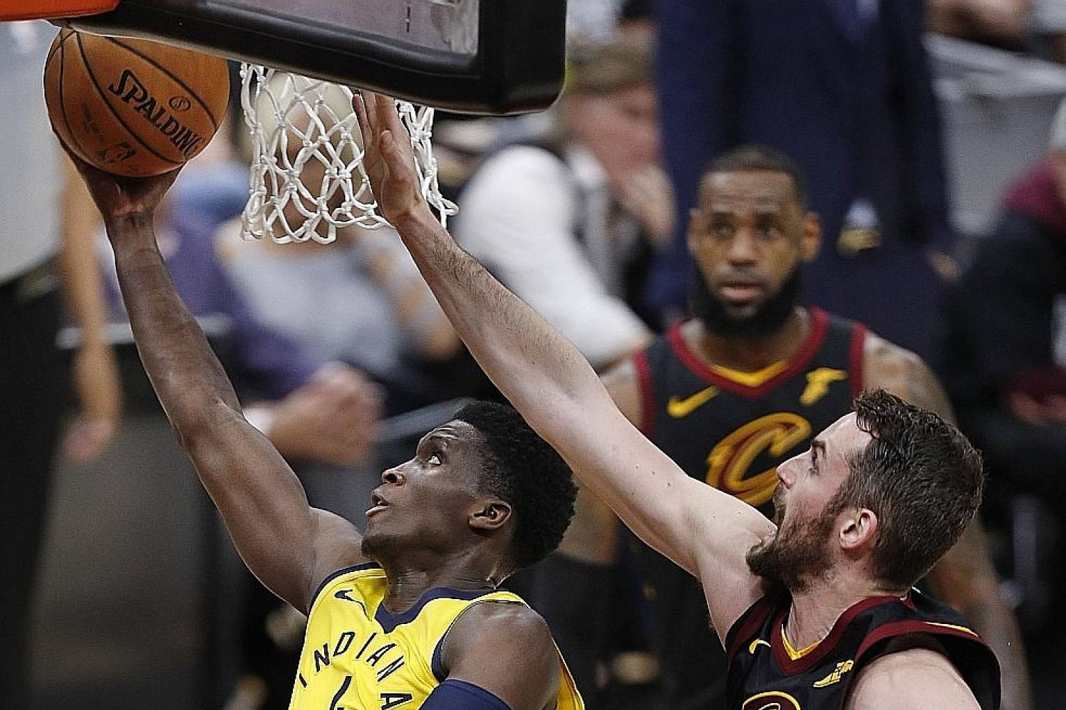 Victor Oladipo of the Indiana Pacers driving to the basket against the Cleveland Cavaliers' Kevin Love as LeBron James looks on. The Pacers defeated the Cavaliers 98-80 in Game 1 of the first round of their NBA Eastern Conference play-off series, wit