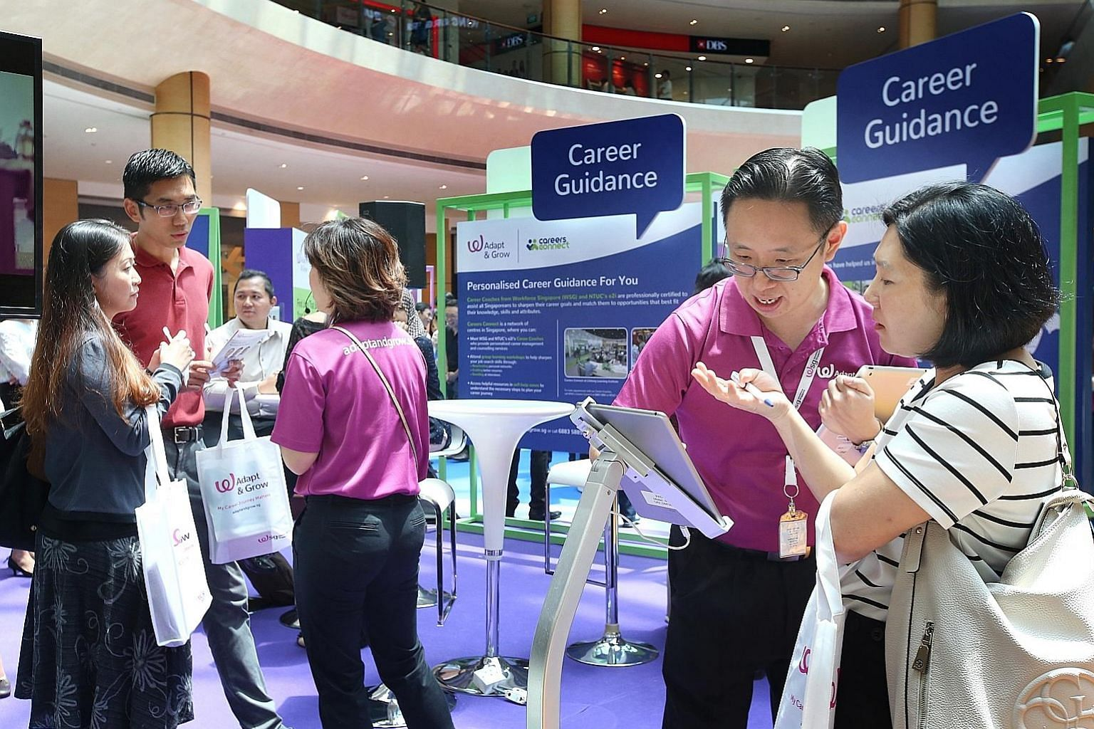 Career coaches (in purple) showing job seekers how to navigate the new MyCareersFuture.sg portal, which replaces the interface of the existing Jobs Bank for users. For now, employers will still post jobs on Jobs Bank, and the posts will be shown on t