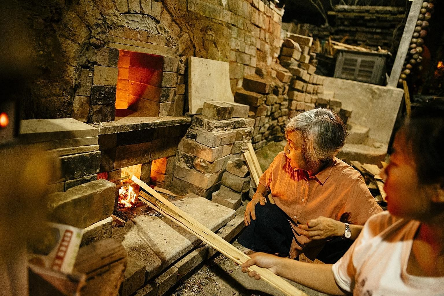 Left: Thow Kwang Industry project director Yulianti Tan, 59, and studio director Stella Tan, 27, stoke the company's dragon kiln. Below: Sam Mui Kuang Pottery is believed to have run one of the first dragon kilns here. It had to make way in 1994 for