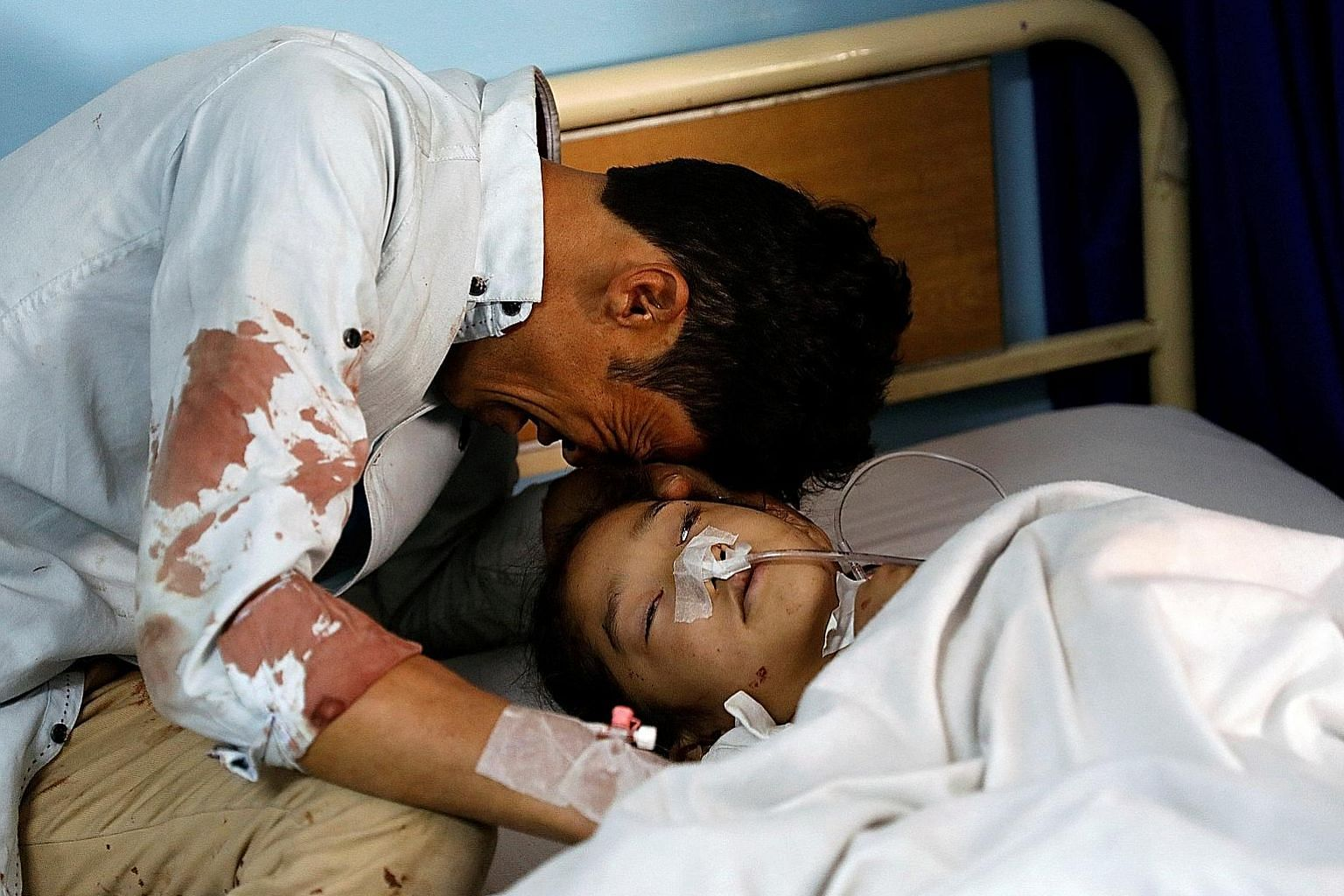 A man crying beside an injured girl at a hospital after the attack in Kabul, Afghanistan.