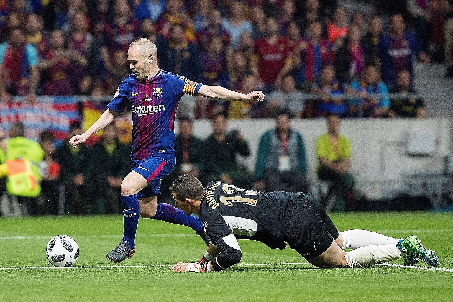 Andres Iniesta rounding Sevilla goalkeeper David Soria to score the fourth goal in Barcelona's 5-0 victory in the King's Cup final in Madrid.