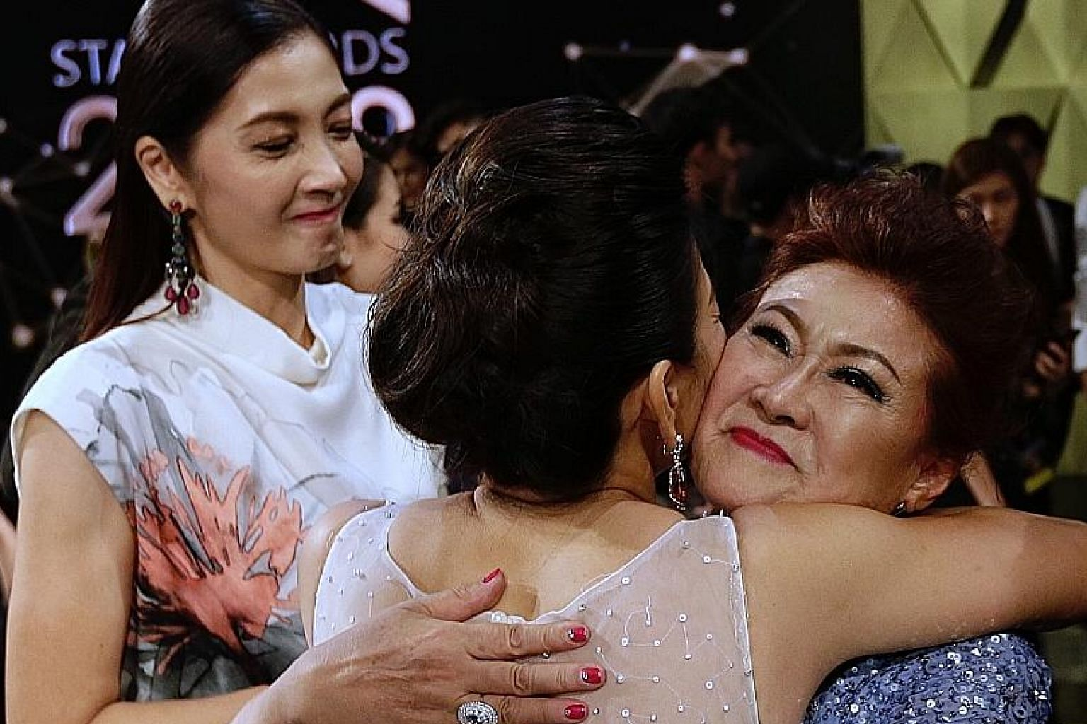 Veteran actress Jin Yinji receives a hug from radio deejay Wendy Zeng last night. She was named one of the Top 10 Most Popular Female Artists for the first time. With them is actress Huang Biren.