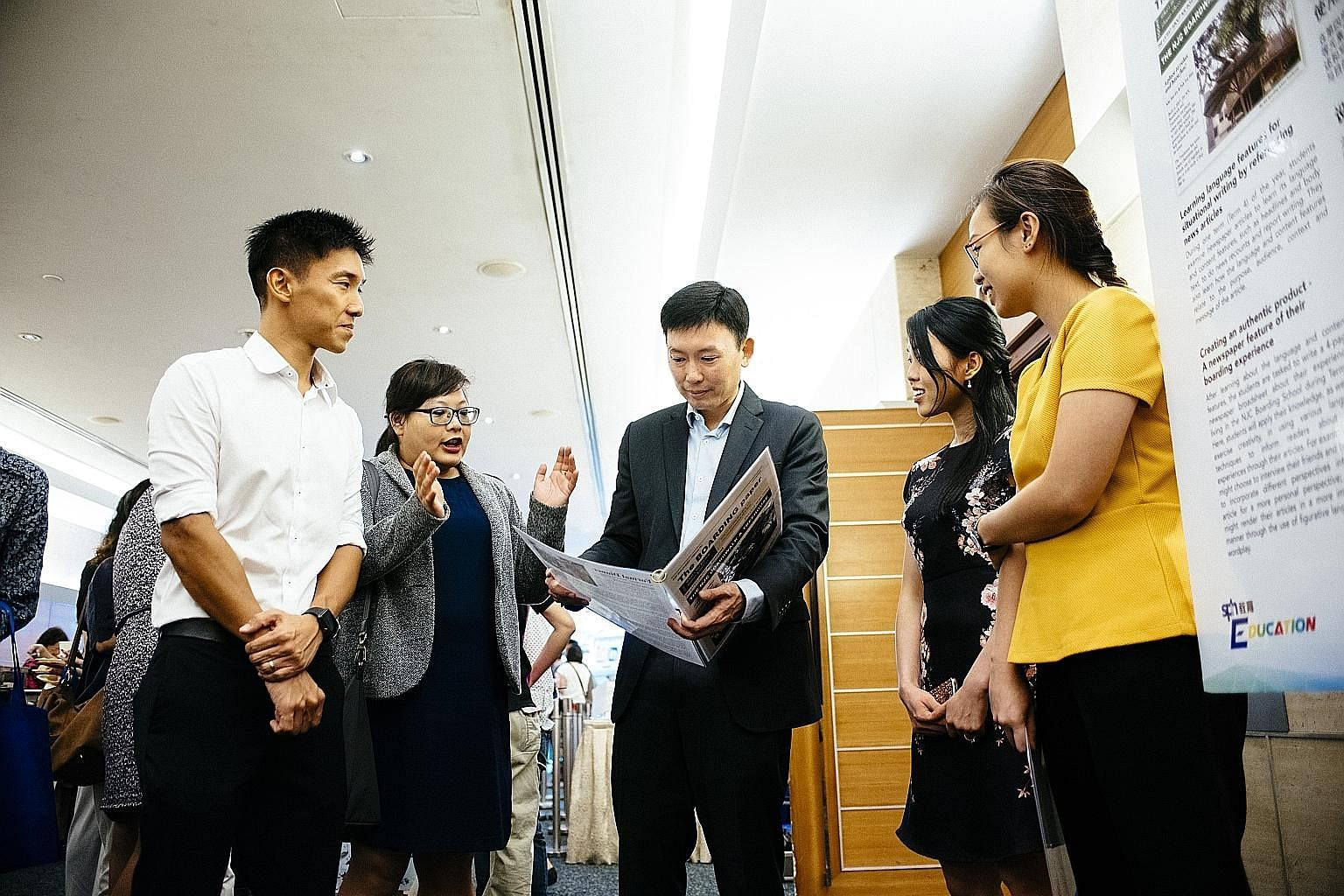 Senior Minister of State for Communications and Information and Health Chee Hong Tat looking at a newsletter put together by students involved in a National Junior College (NJC) project. With him are (from left) The Straits Times Schools teaching spe
