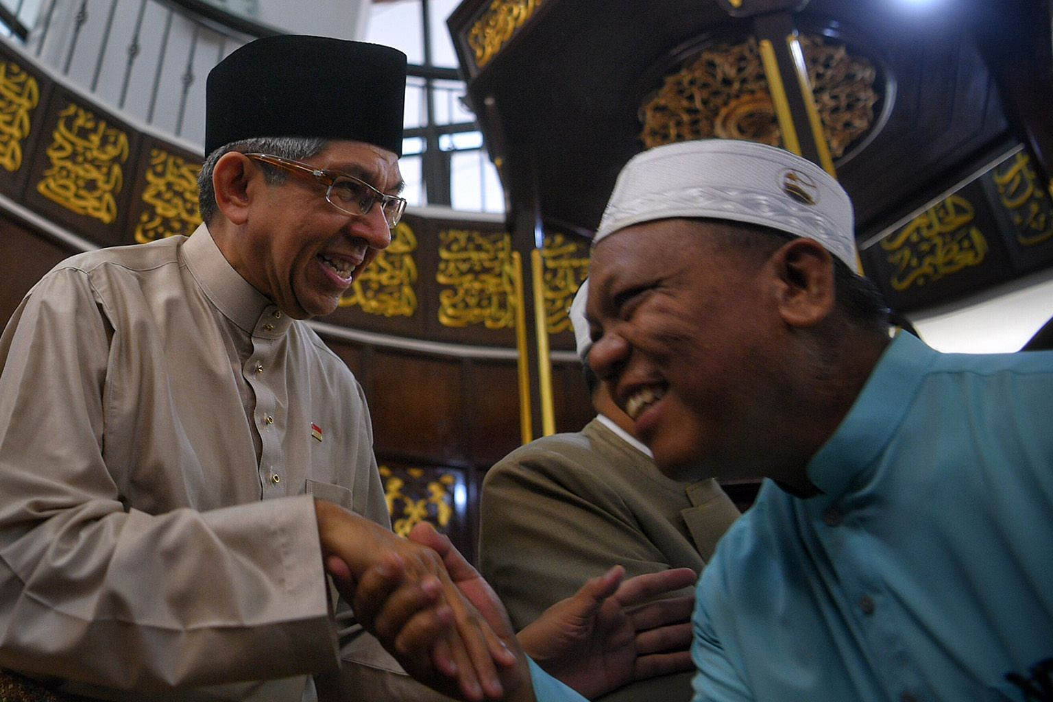 "Dr Yaacob Ibrahim greeting a congregant at Al-Mukminin Mosque in June last year. Noting the progress made by the Malay/Muslim community, the 62-year-old says: ""Now, it's how we can push that even higher."""