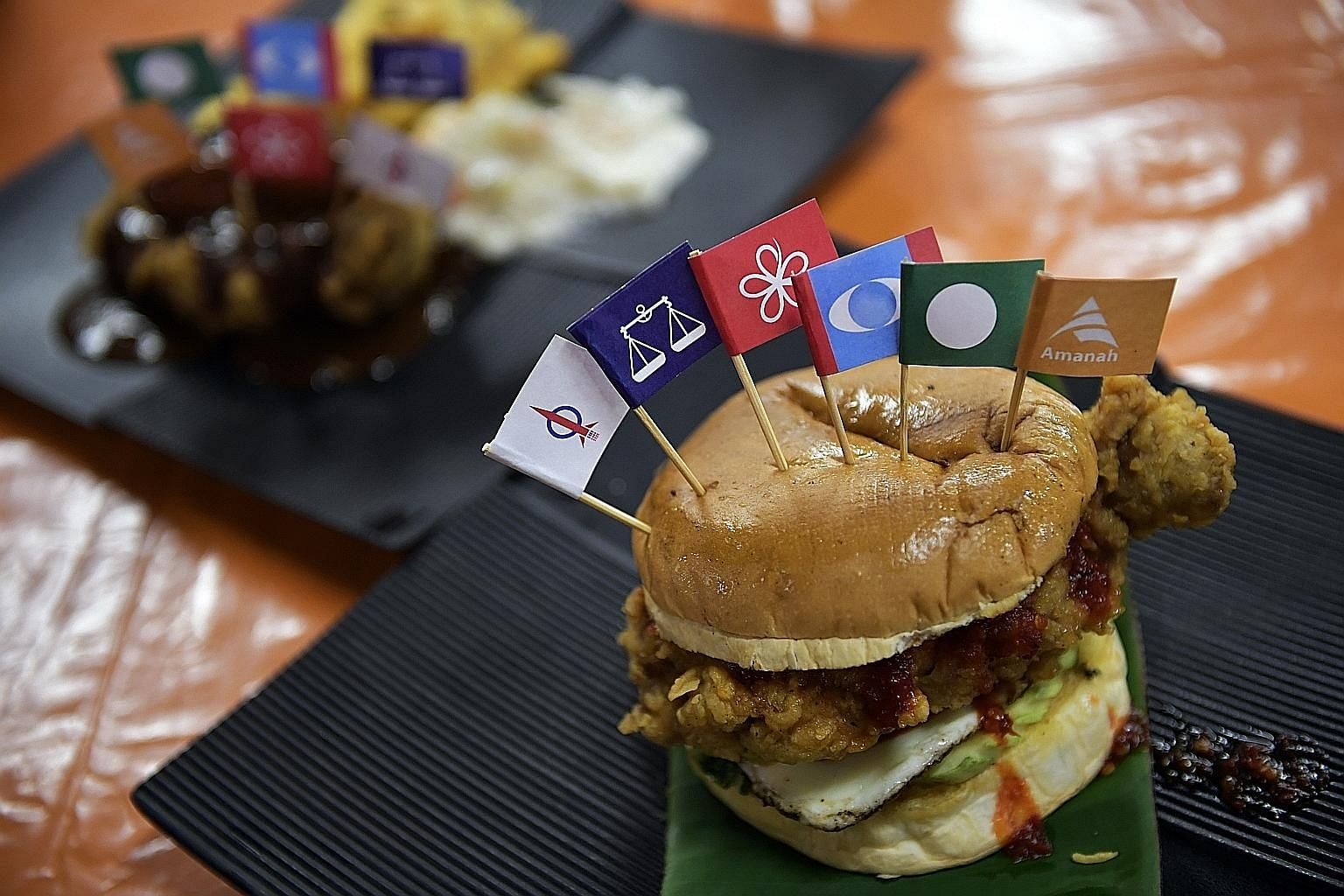 Party flags on the nasi lemak burger at Uncle Lan'z where employees pick a flag at random to stick on a dish.