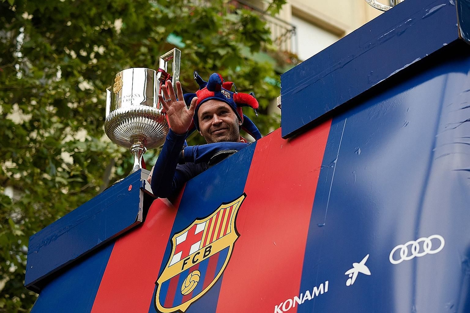 Andres Iniesta waving from an open-top bus during Barcelona's parade to celebrate their 25th La Liga title on Monday. The 34-year-old midfielder is leaving his only club at the end of the season and will have no shortage of suitors from outside Europ