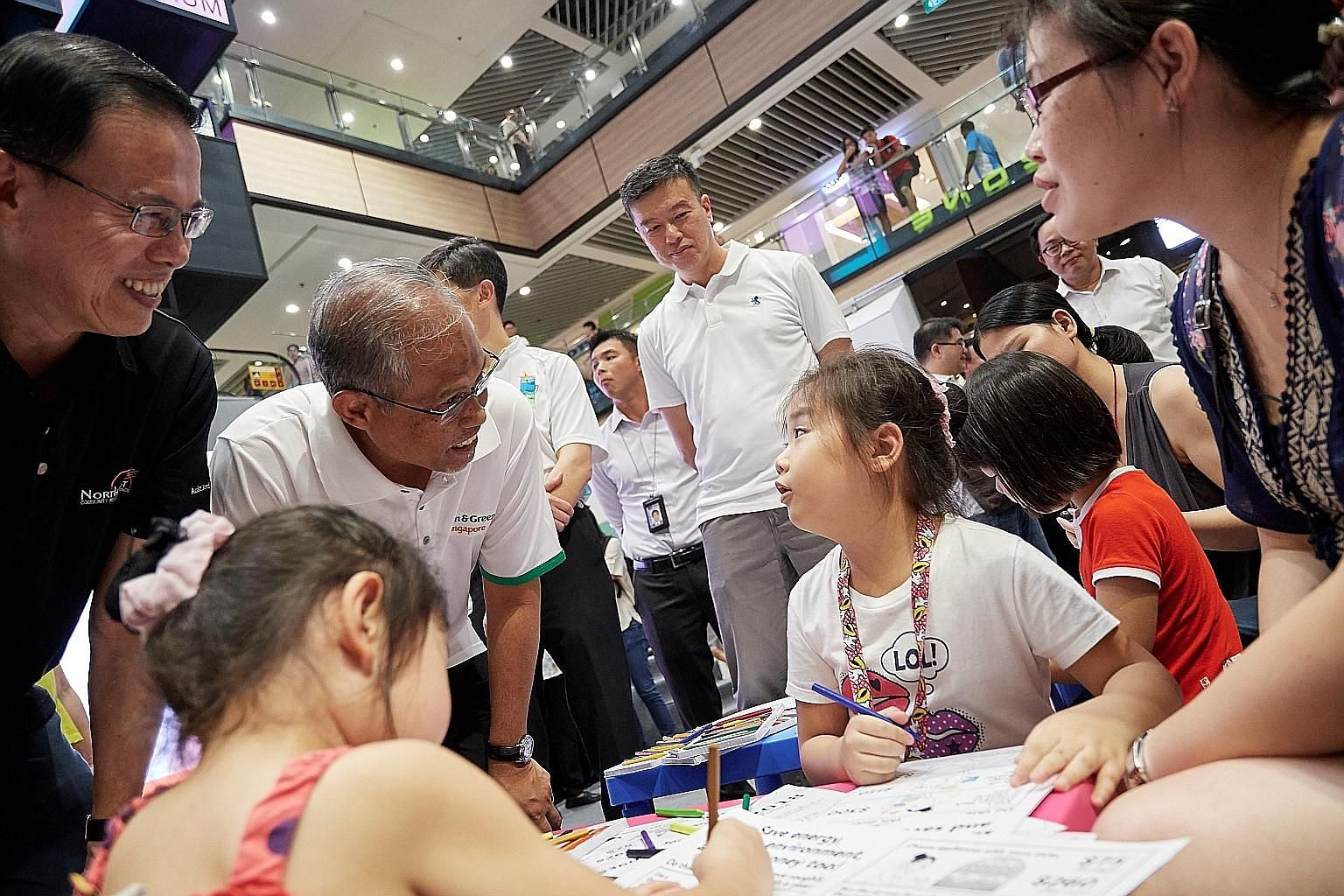 Environment and Water Resources Minister Masagos Zulkifli and North West District Mayor Teo Ho Pin (far left) chatting with Yishun resident Charlene Ng, seven, at the Energy-Saving Challenge launch.